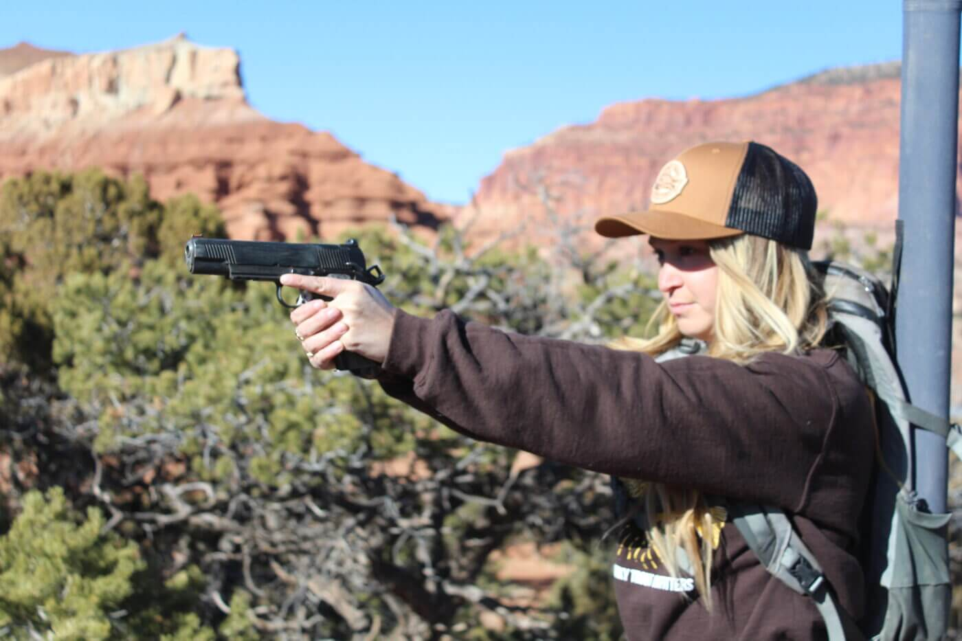 Blonde woman shooting a 1911 chambered for the 10mm cartridge