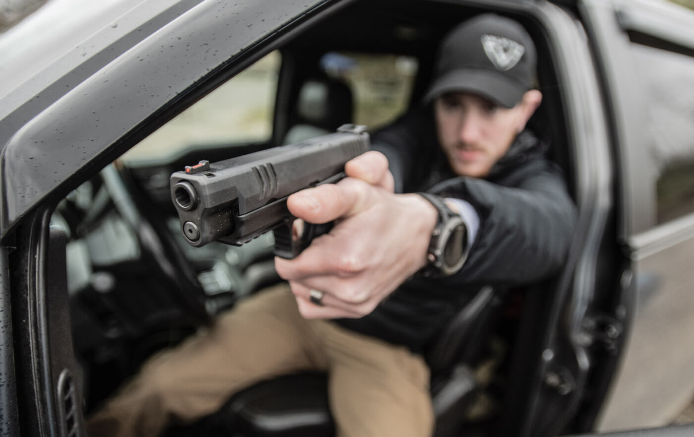 Police officer shooting a 10mm Springfield XD-M from his patrol car