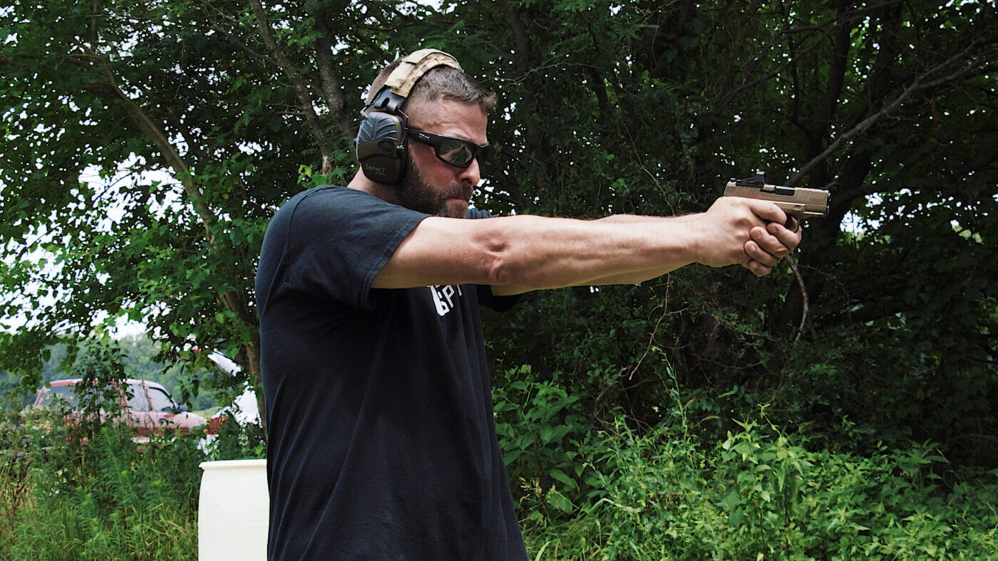 Side view of author with Hellcat handgun at extension