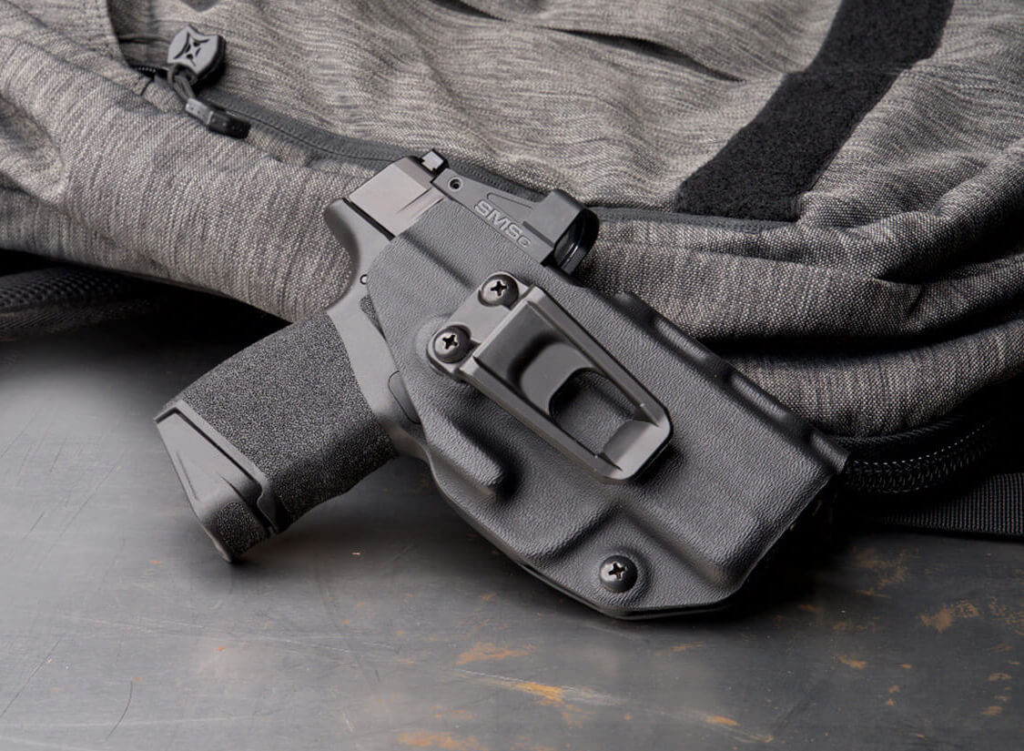 Shown in a holster, this Springfield Hellcat is equipped with a red dot optic