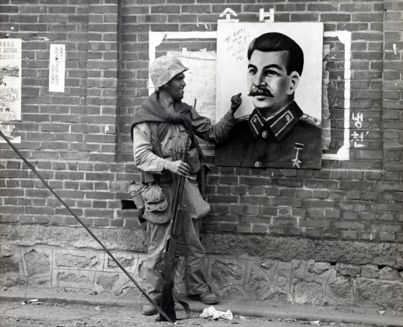 Marine with a BAR in Korea in front of a Joseph Stalin poster
