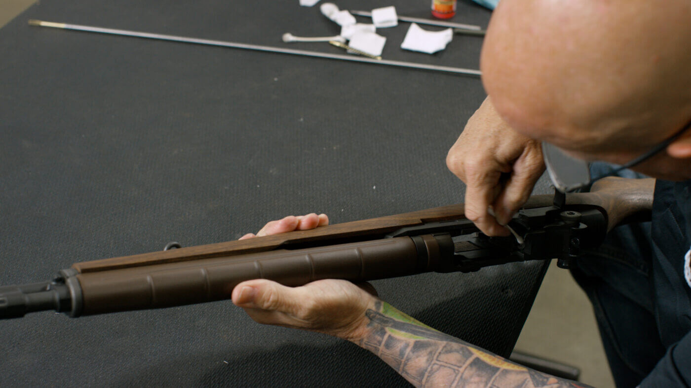 Cotton swab cleaning the bolt face of an M1A