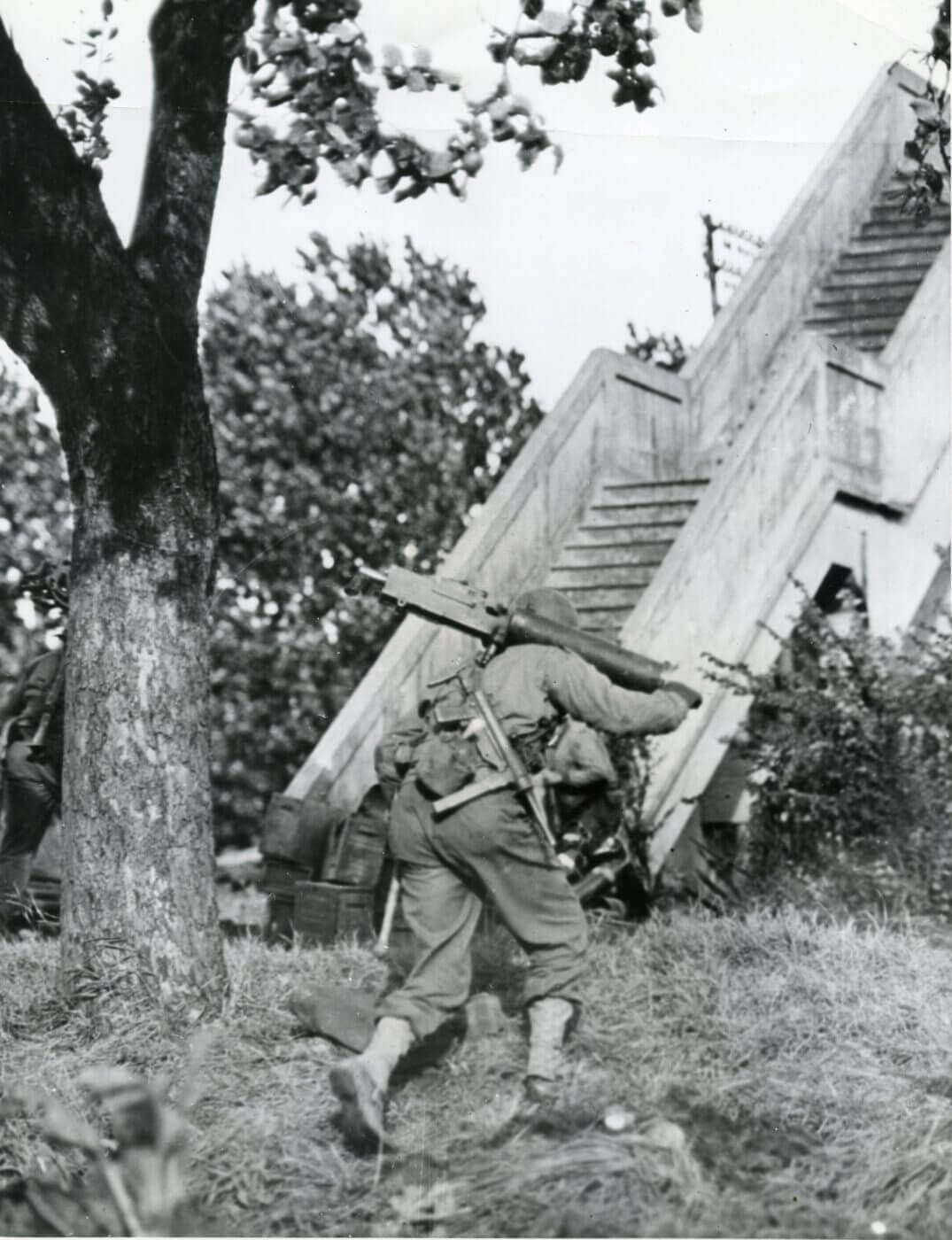 A Browning M1917 machine gunner carries a M3 SMG