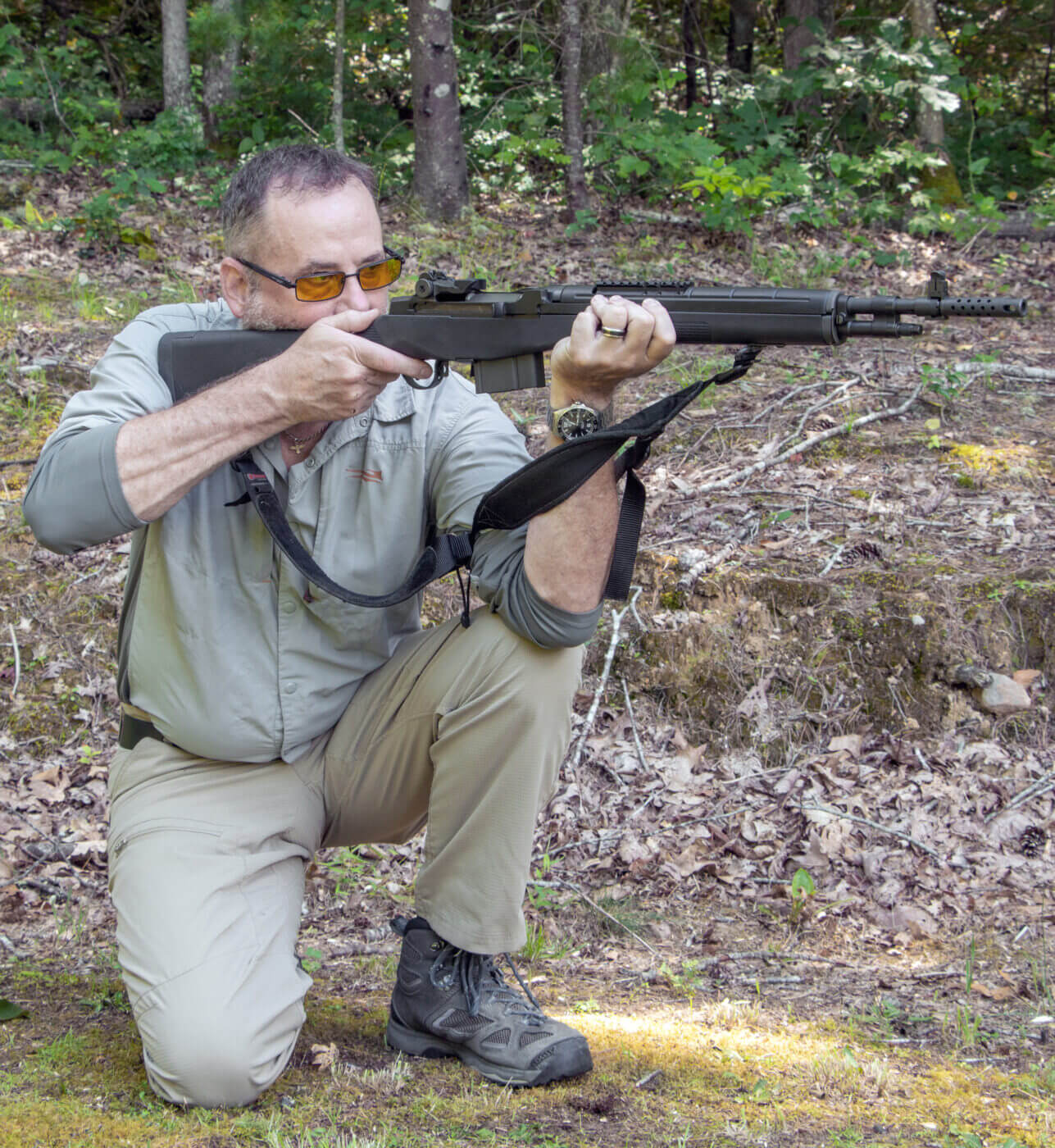 Man showing how to shoot a rifle while kneeling