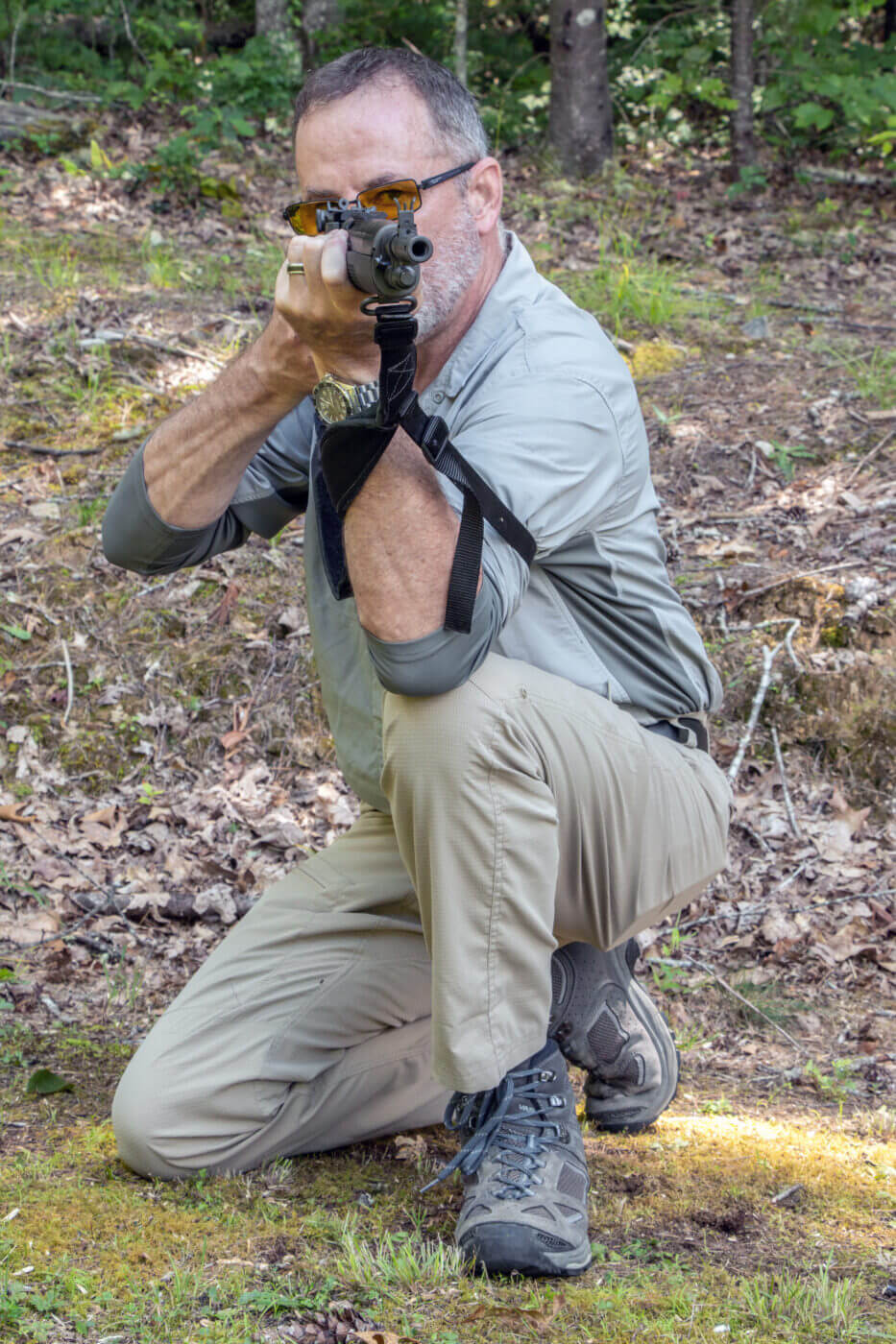 Man instructs how to shoot a rifle from a kneeling position