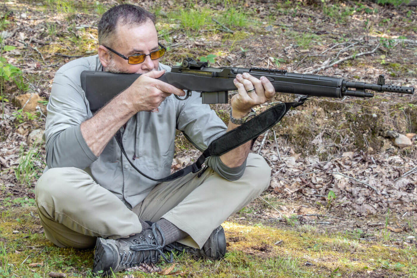 Man demonstrates how to shoot a rifle while sitting