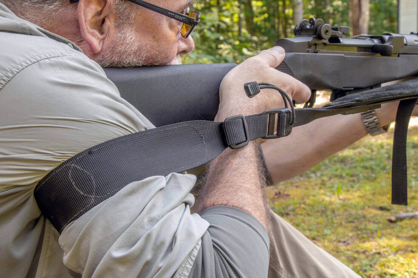 Man teaching how to use a sling while shooting a rifle from a sitting position