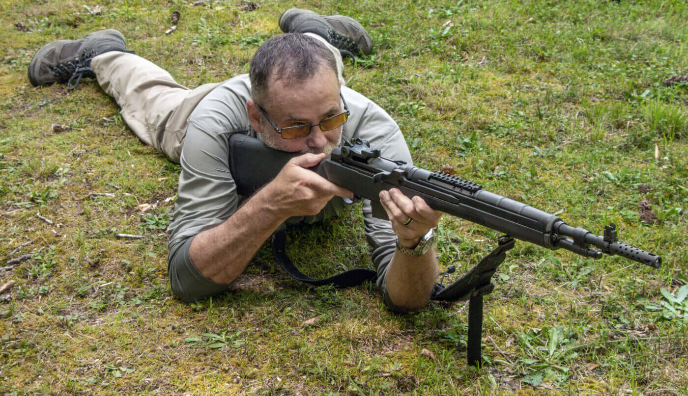 Instructor demonstrates shooting a rifle from a prone position
