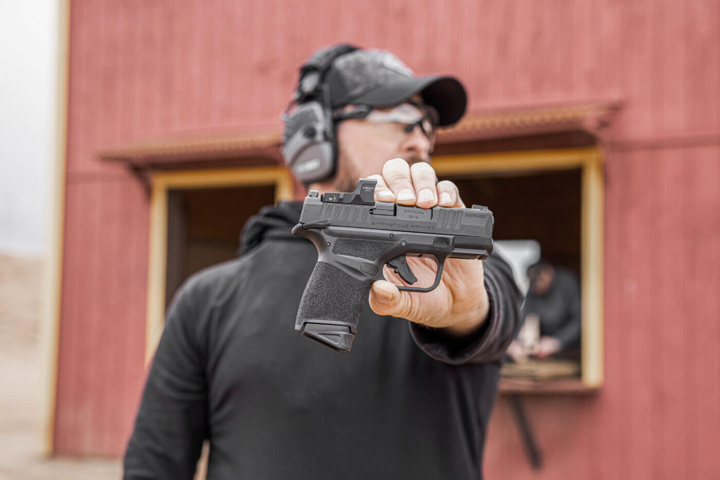 Holding a Springfield Hellcat pistol in front of building