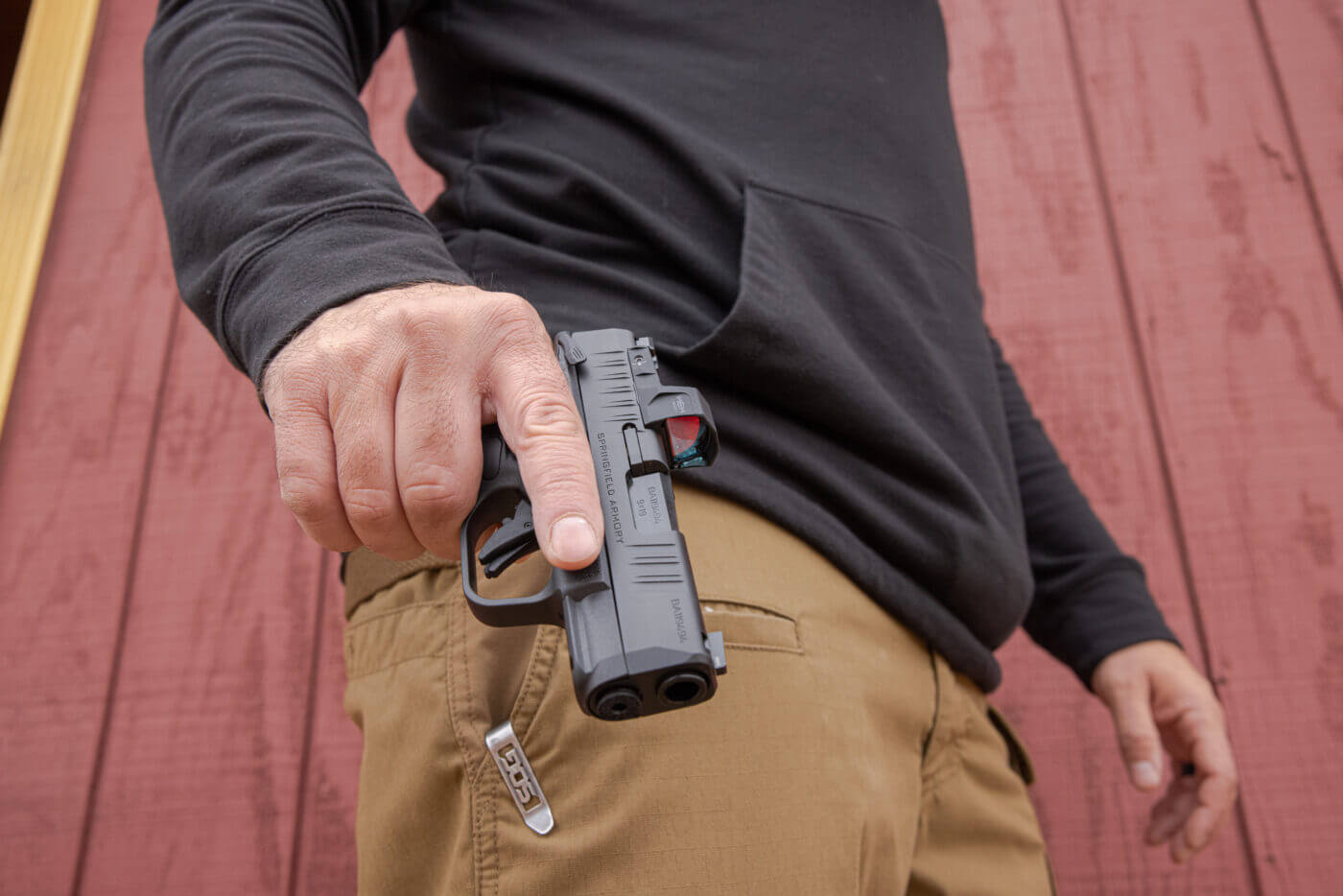 Man carrying a Hellcat pistol in his right hand