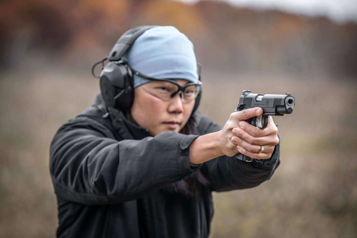 Woman shooting Range Officer Elite 10mm in competition