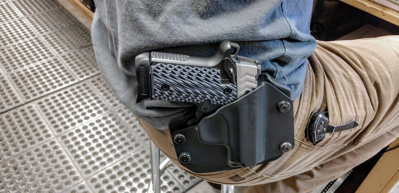 Person seated with Springfield 911 pistol in holster