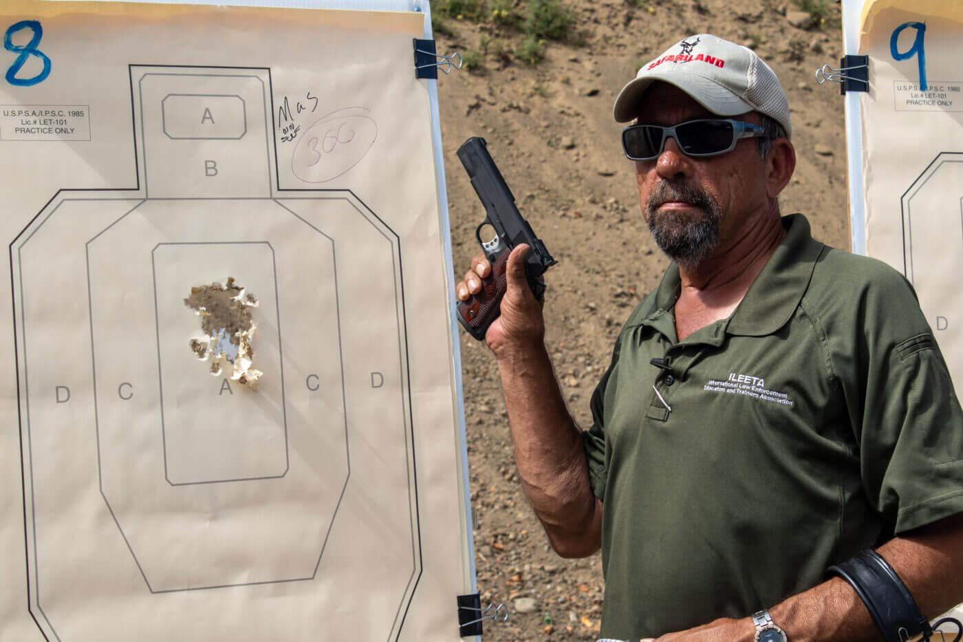 Massad Ayoob with Springfield .45 pistol and ragged target grouping