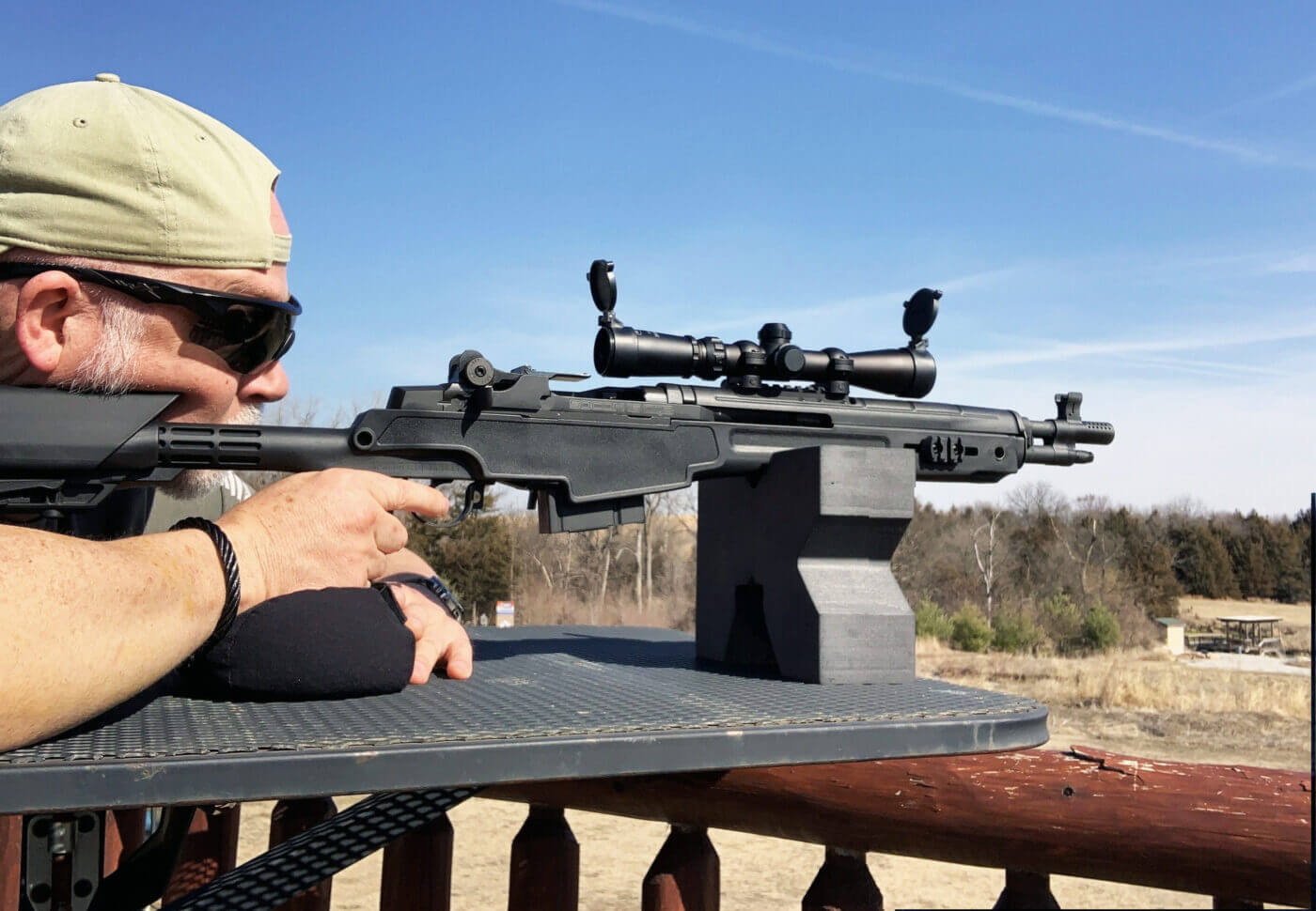 Man shooting rifle with scout scope on M1A SOCOM 16 CQB rifle