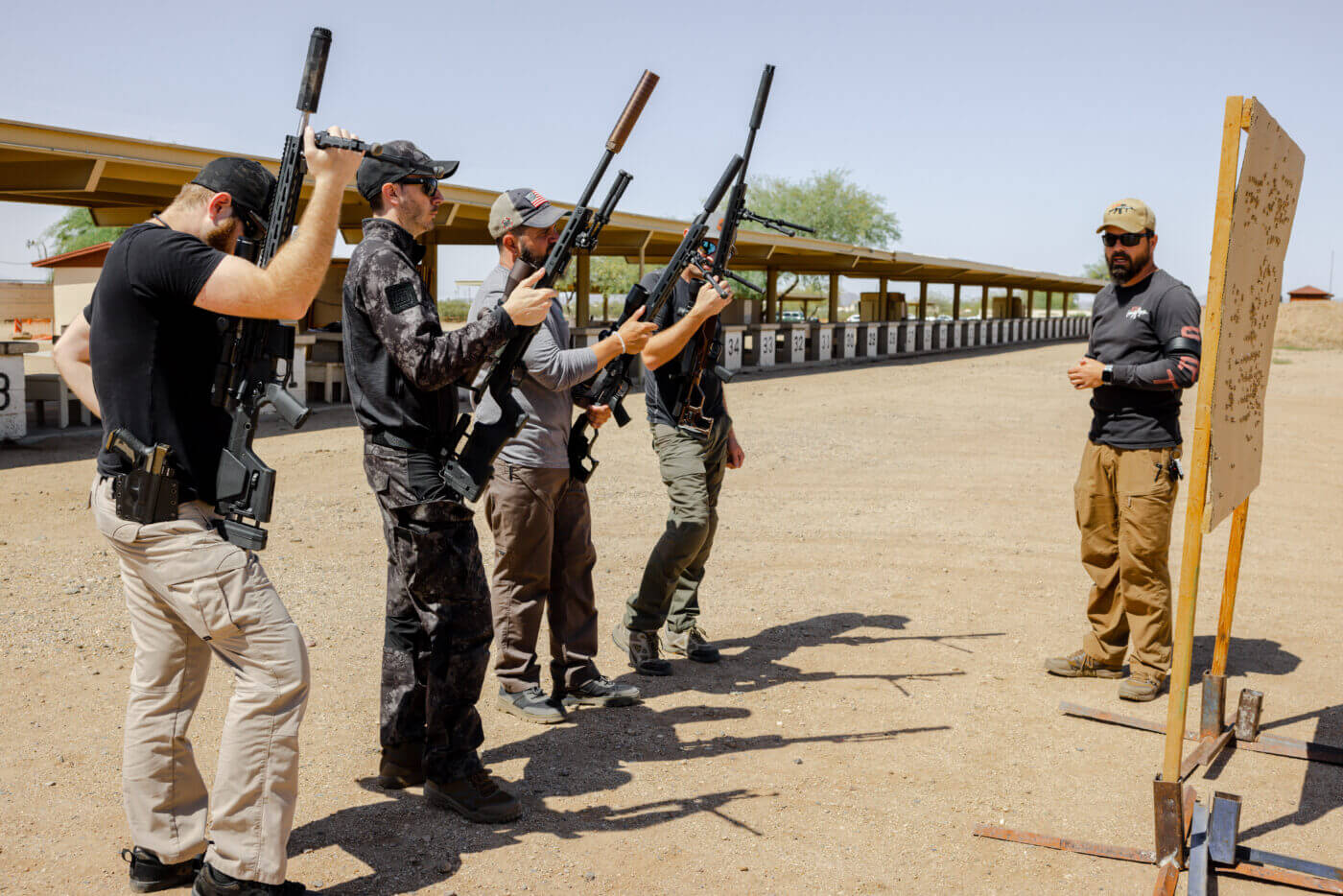 Men standing with rifles while being instructed at precision rifle school