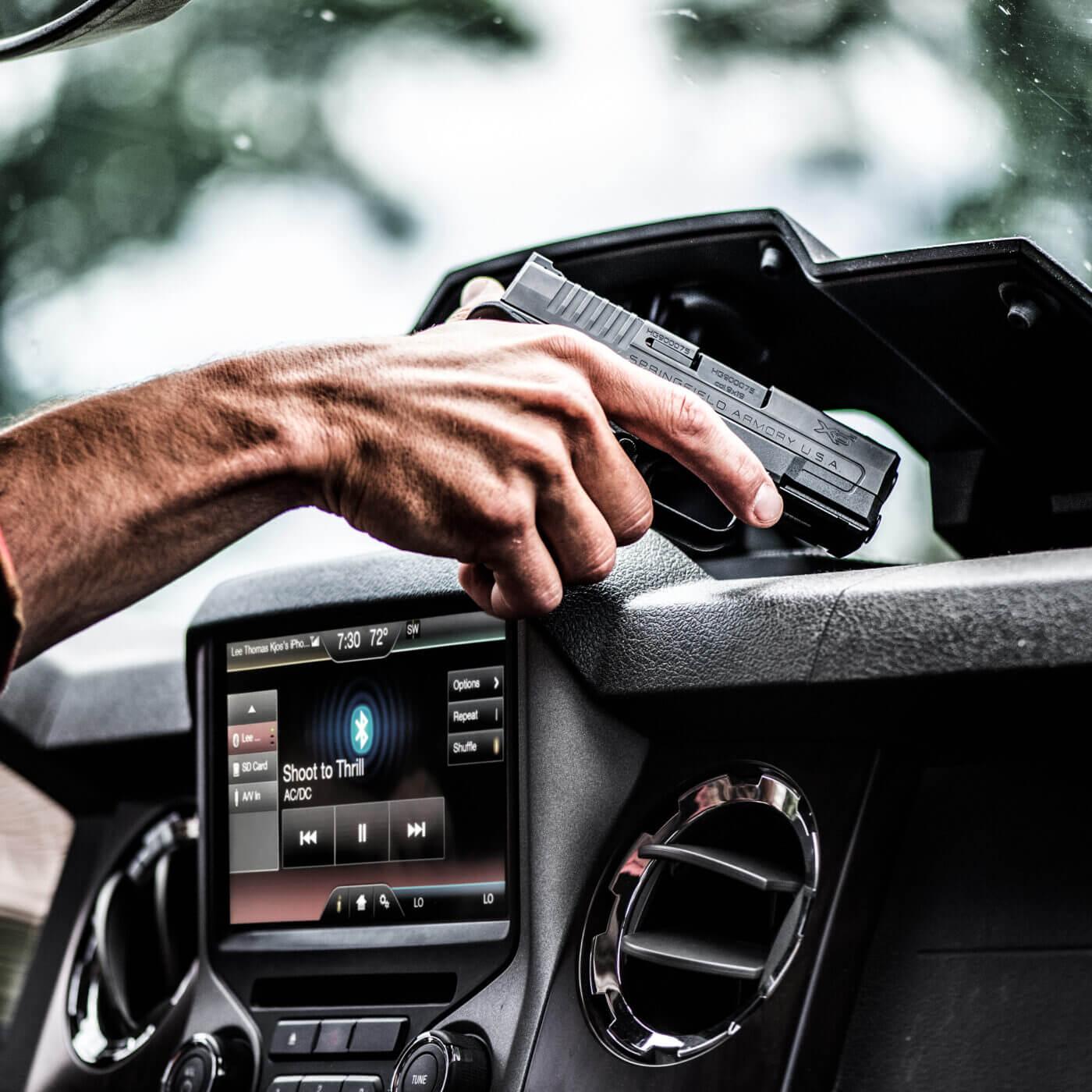 Man holding gun in vehicle
