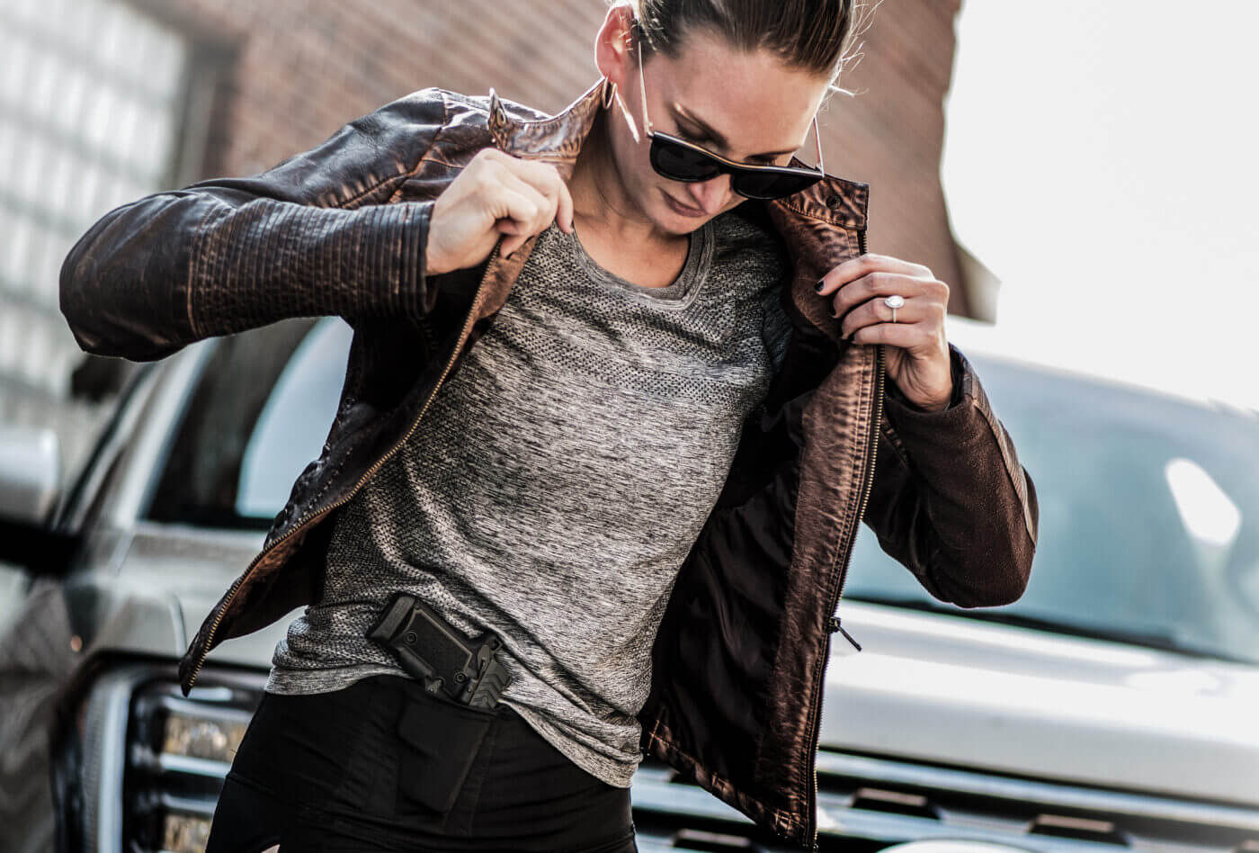 Woman putting on jacket with gun in waistband holster