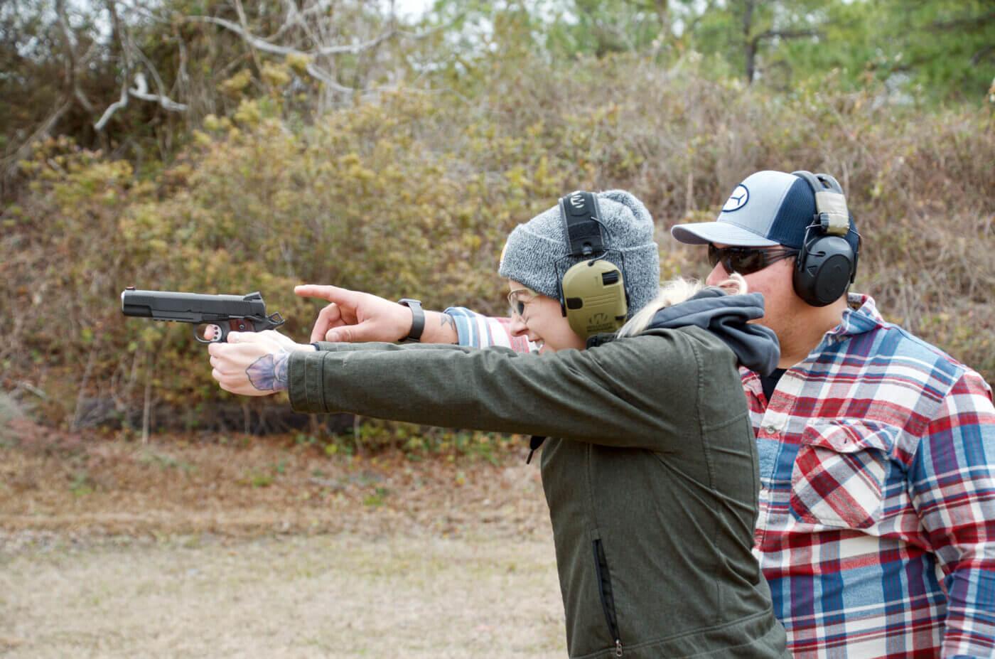Man teaching a new shooter with a 1911 pistol