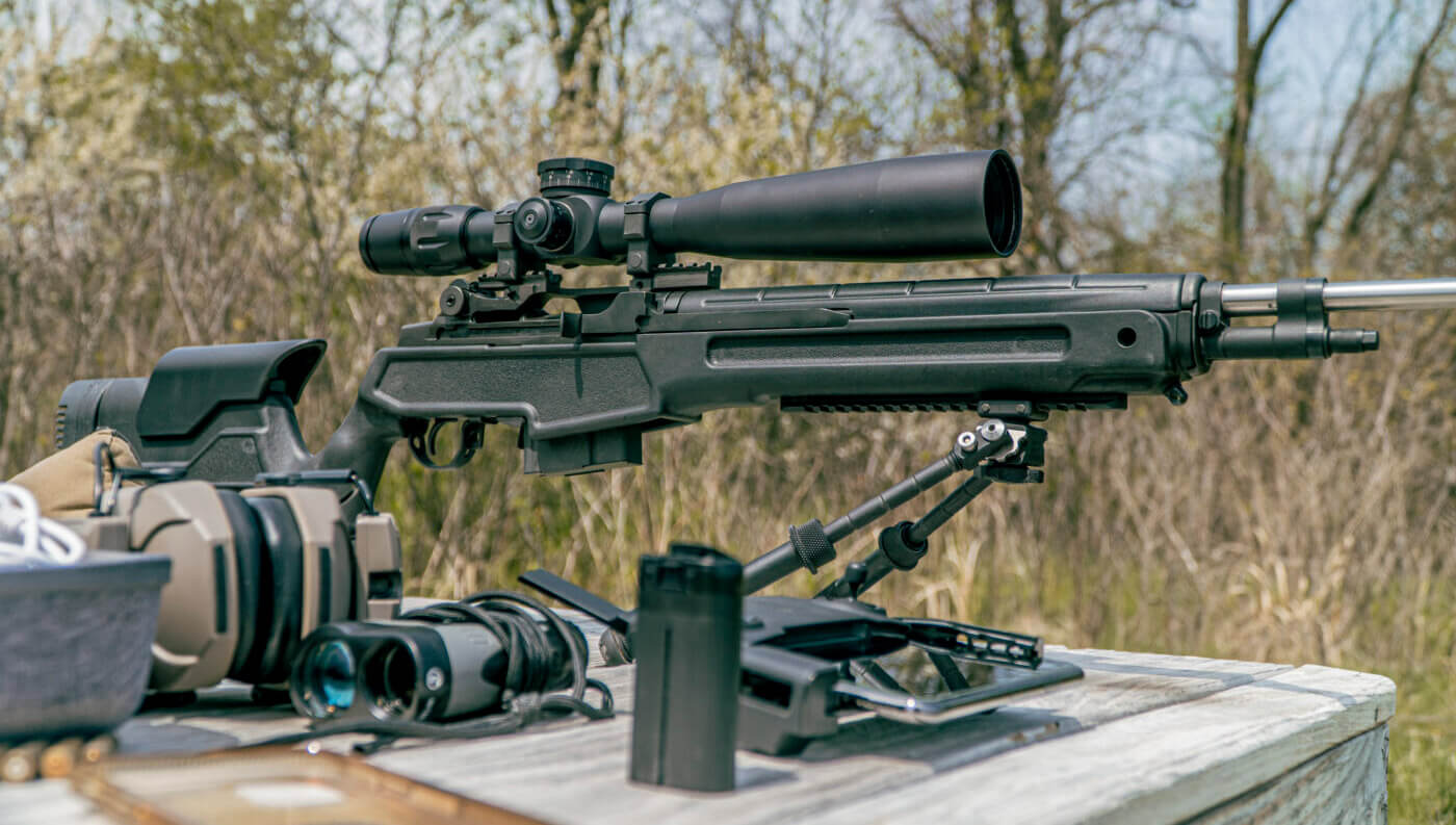 Springfield M1A rifle with scope on table at range