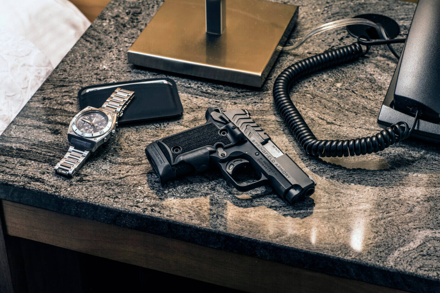 A Springfield 911, a wallet, and a watch on a nightstand