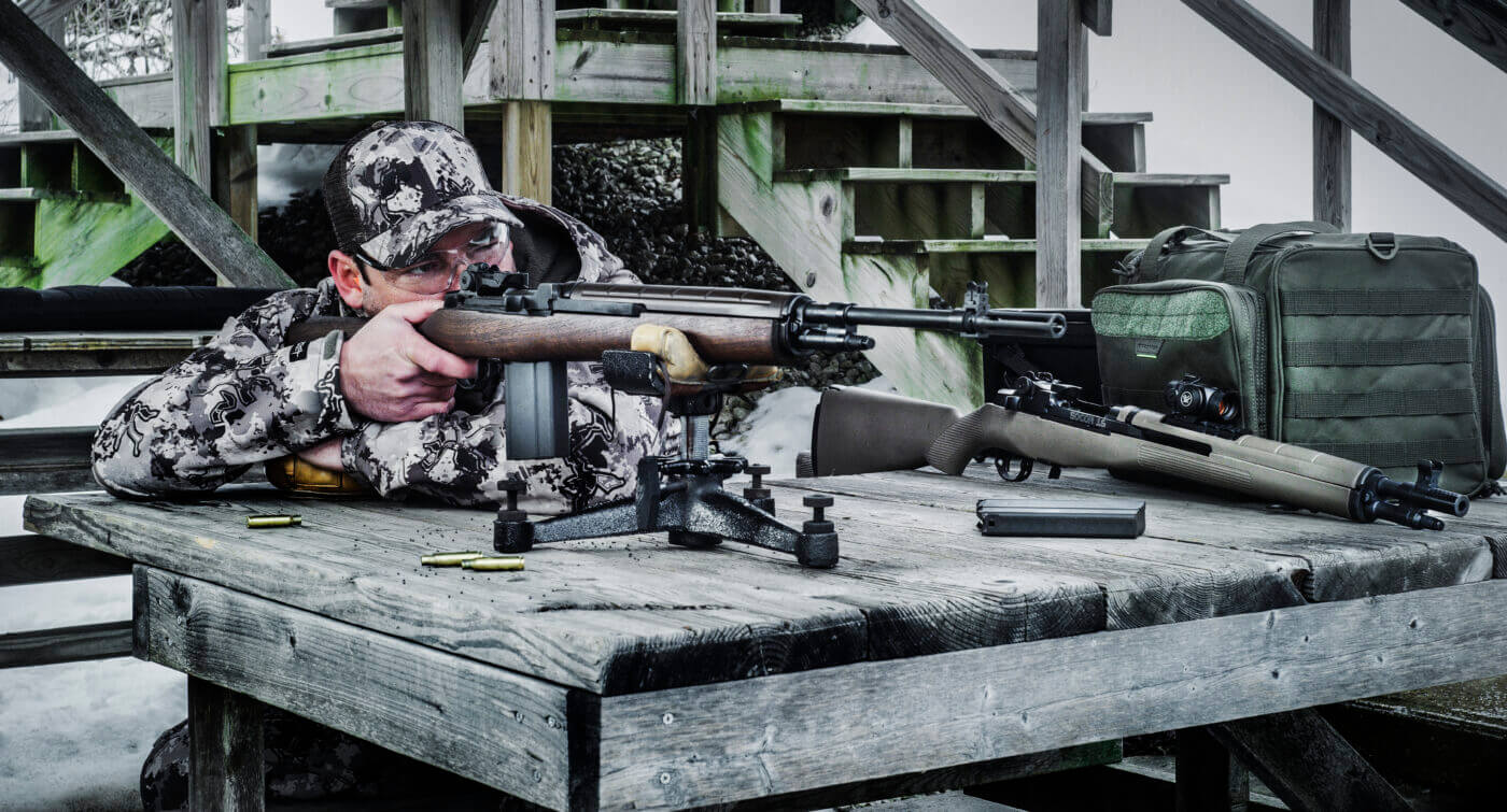 Man shooting rifle from test bench