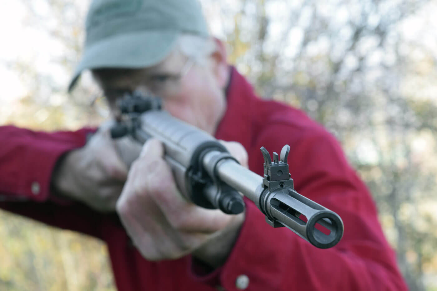 Man in red shirt holding a semi-automatic M1A rifle