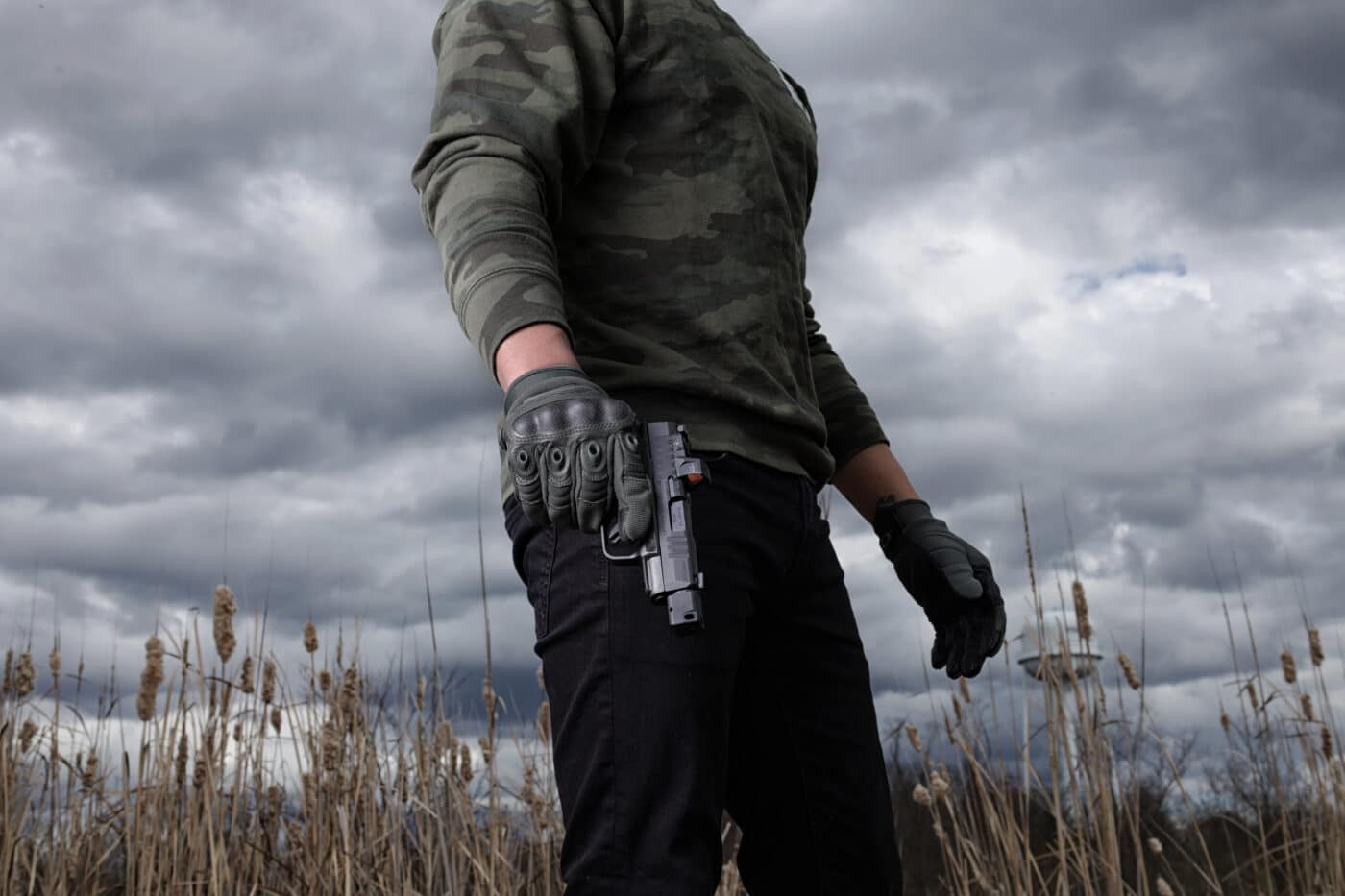 Man in gloves holding  a Springfield Armory Hellcat with HEX Wasp optic mounted