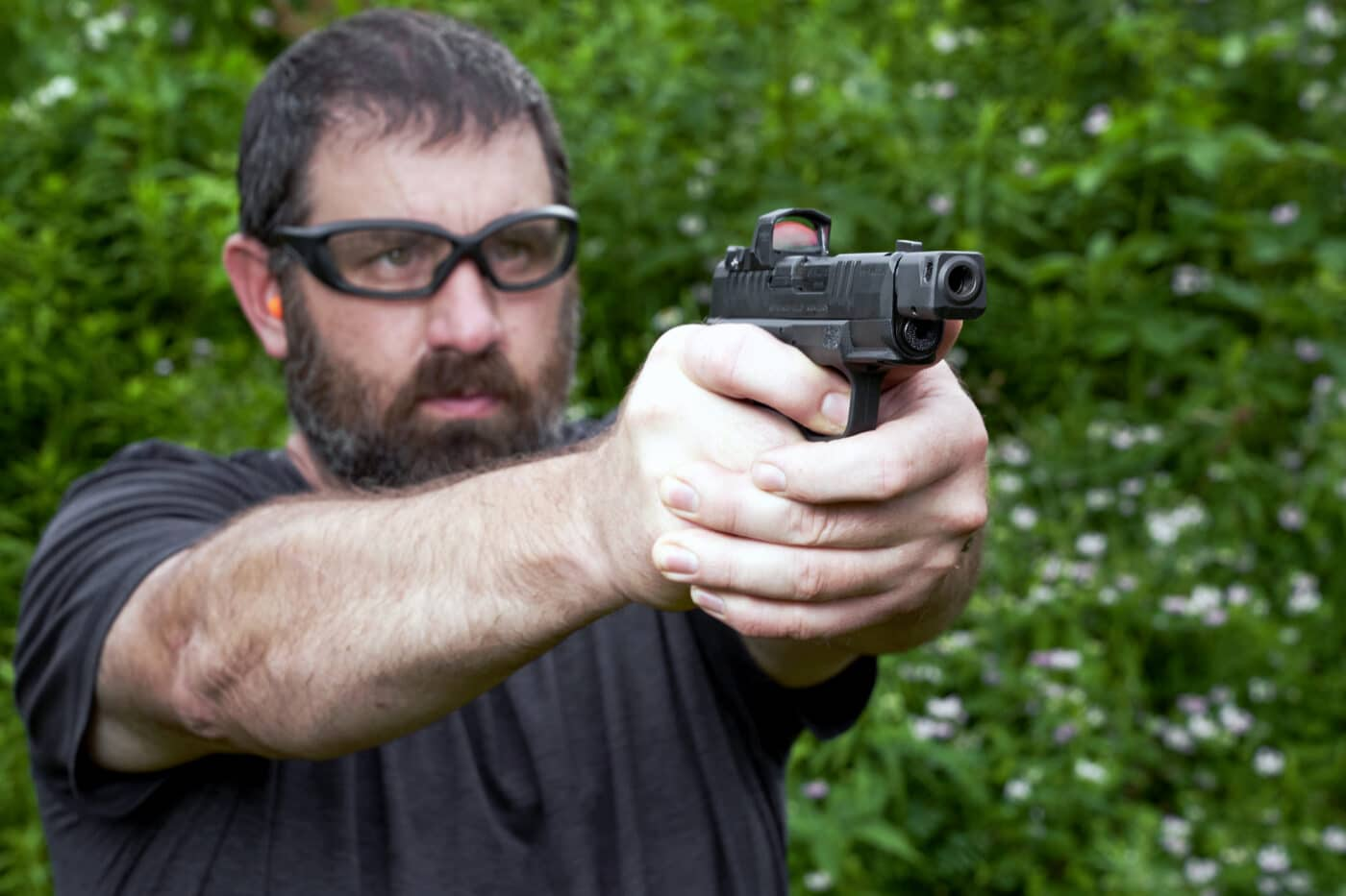Man shooting a Hellcat RDP pistol with HEX Wasp optic mounted on it