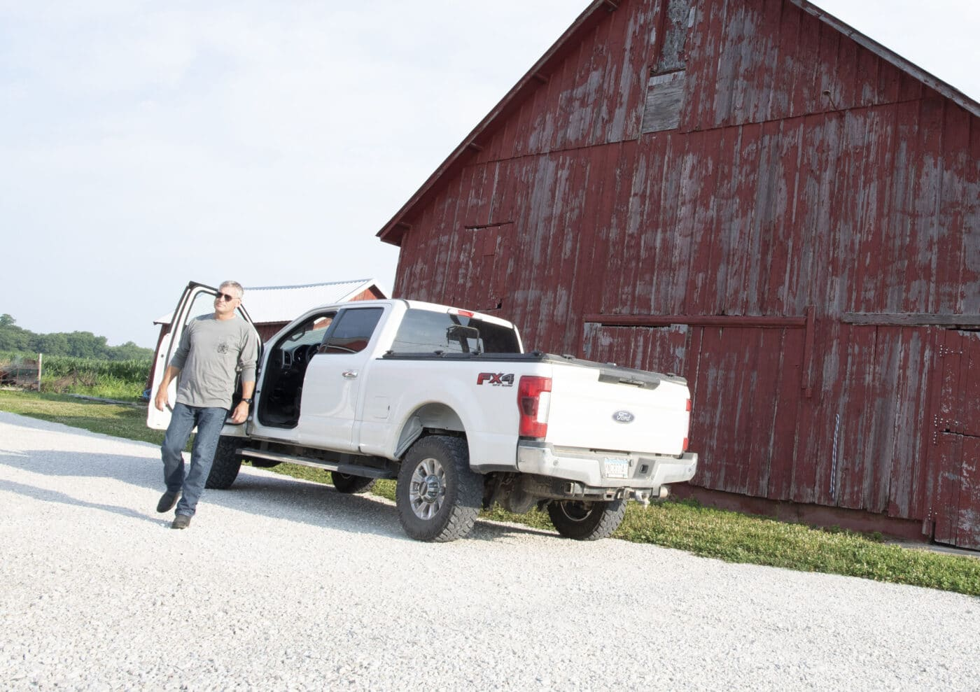 Man on farm property with truck and barn