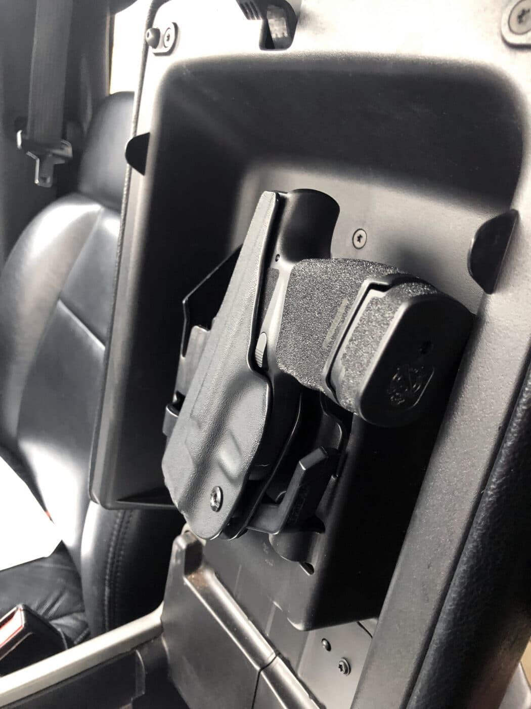 Springfield Hellcat pistol in a concealment holster inside a truck
