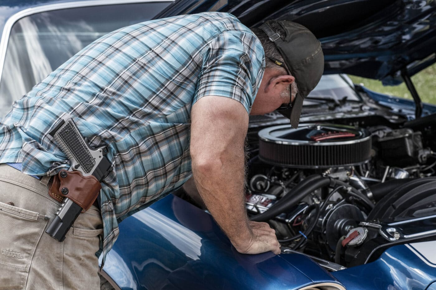 Man working on car while carrying an Emissary 1911 in a Yaqui slide holster