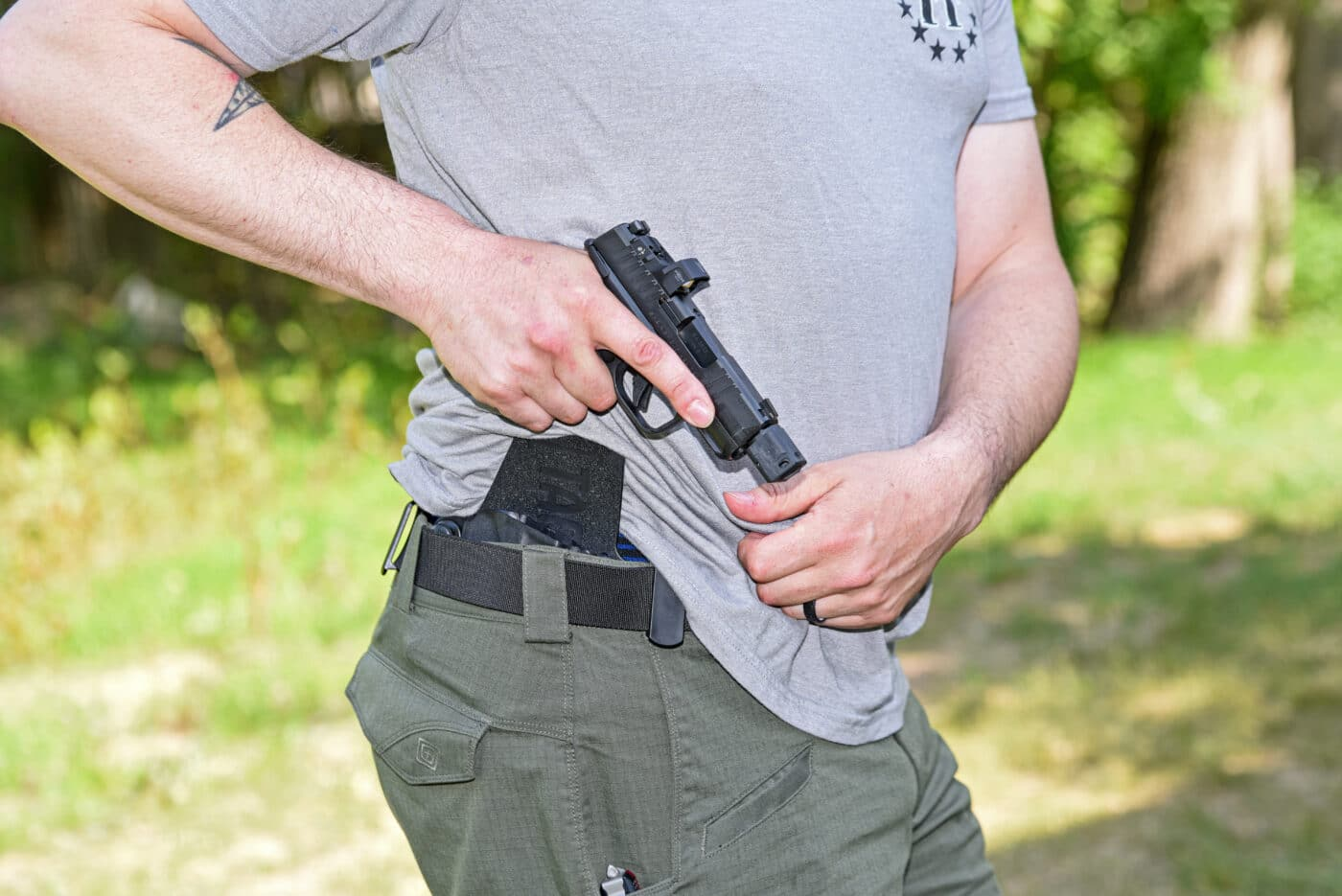 Man drawing a Springfield Hellcat from concealment