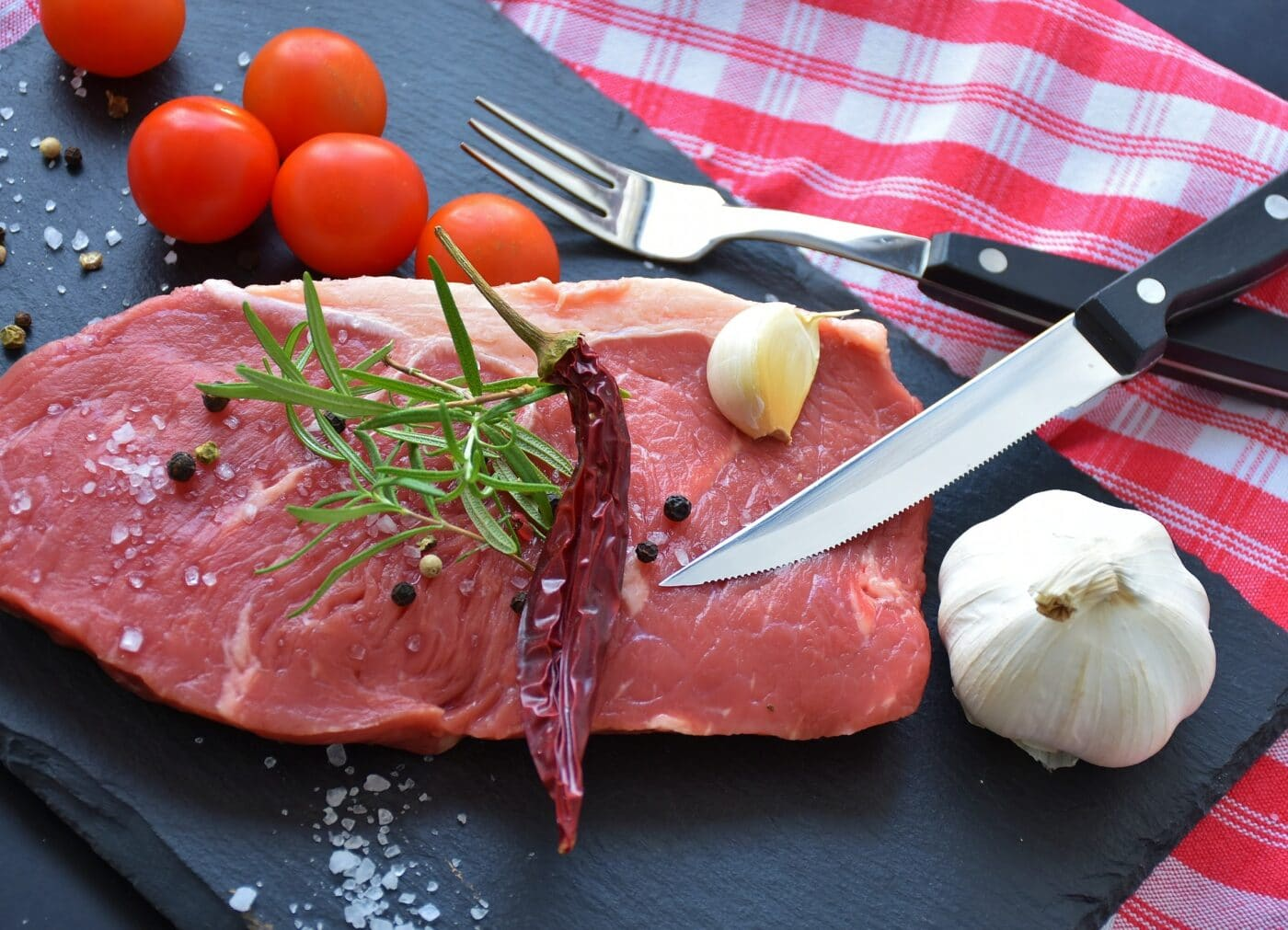 Home processed meat with knife, fork, and herbs