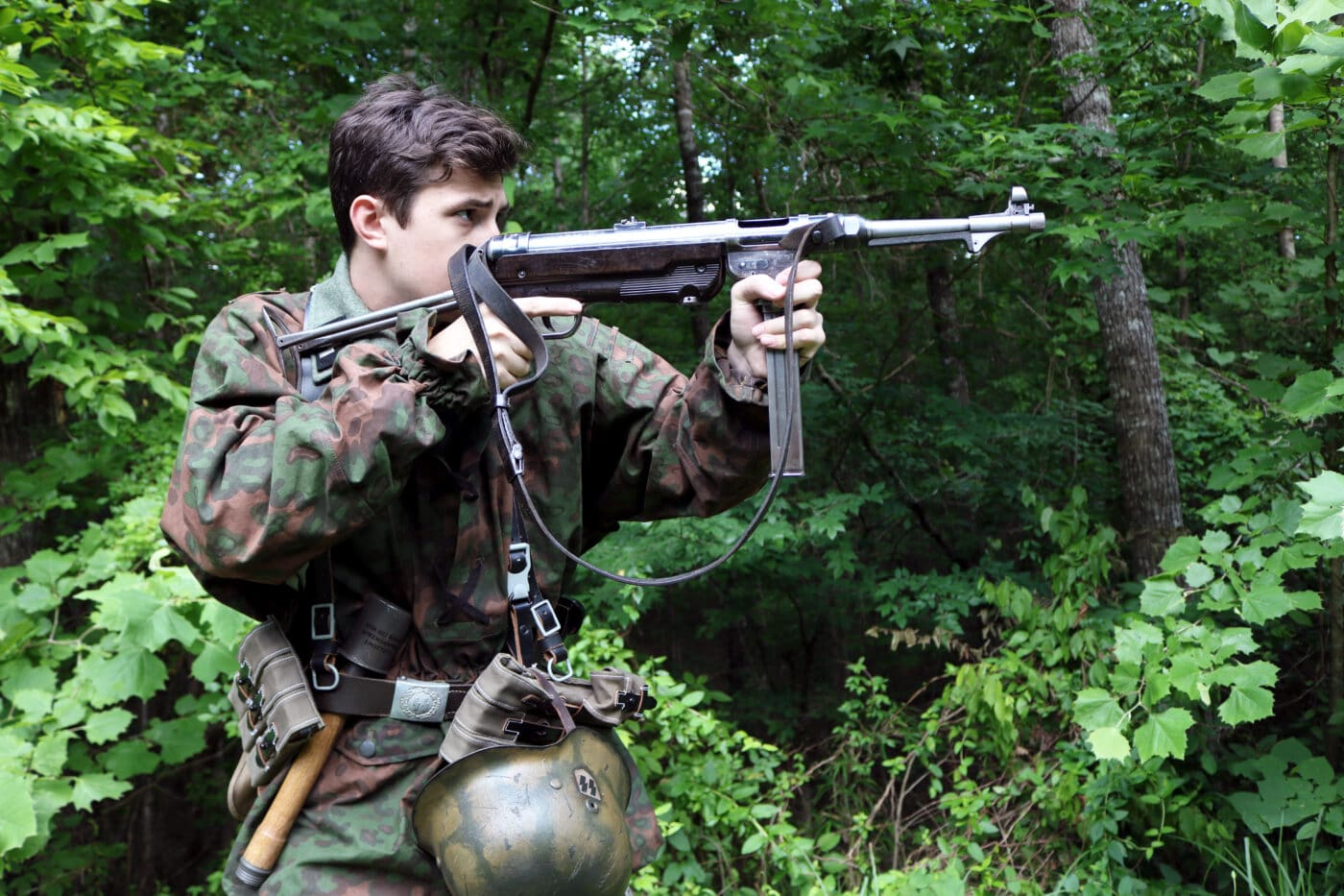 Man dressed as German SS soldier shooting an MP40 SMG