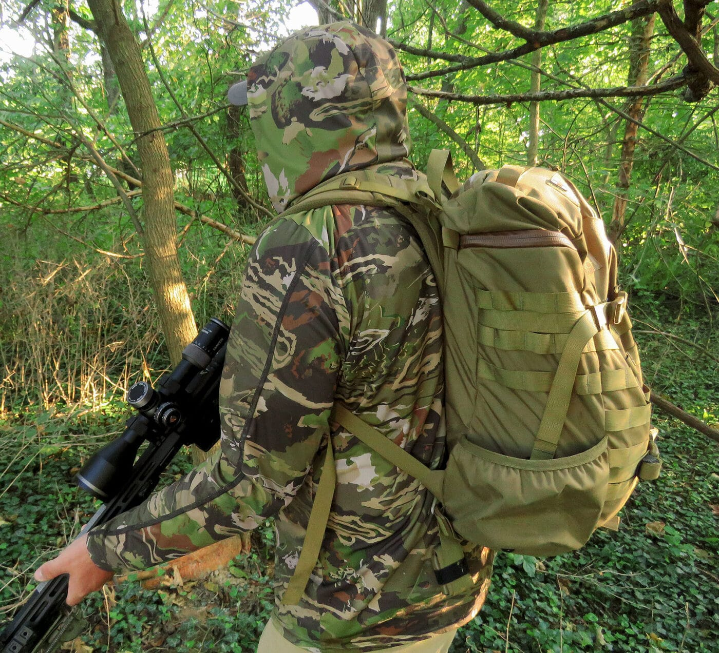 Military-style backpack worn in the woods