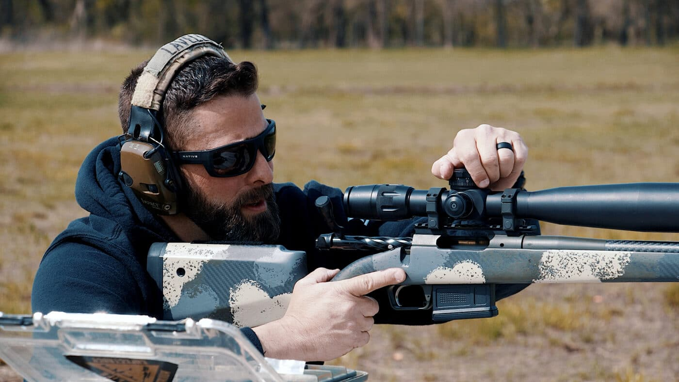 Man adjusting a scope while sighting it in