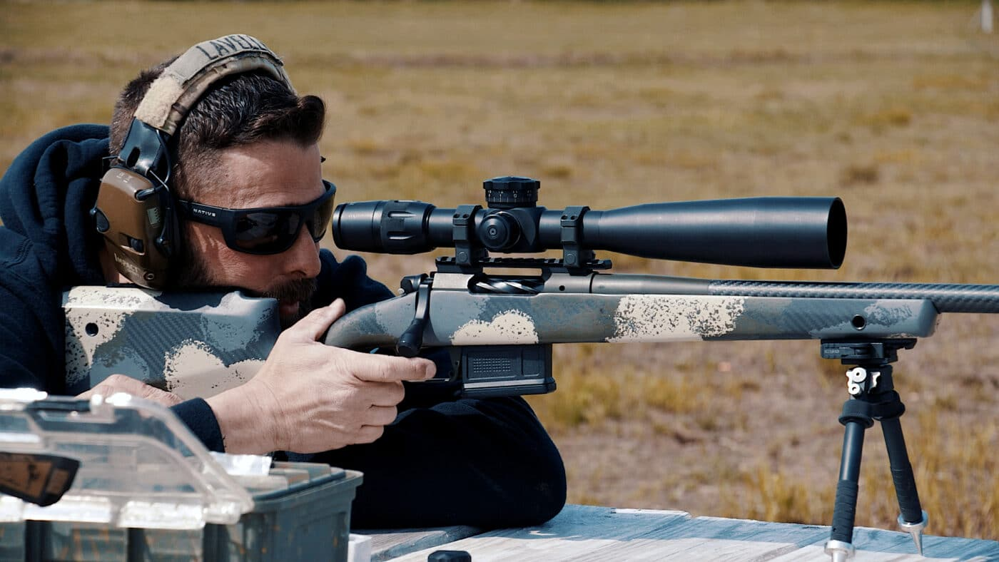 Man shooting a rifle while sighting it in at the range