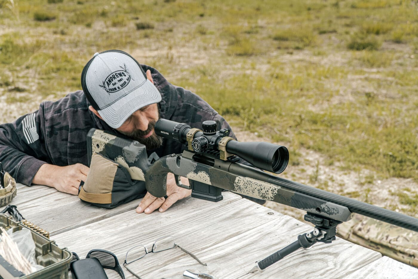 Man shooting a rifle at the range while sighting it in