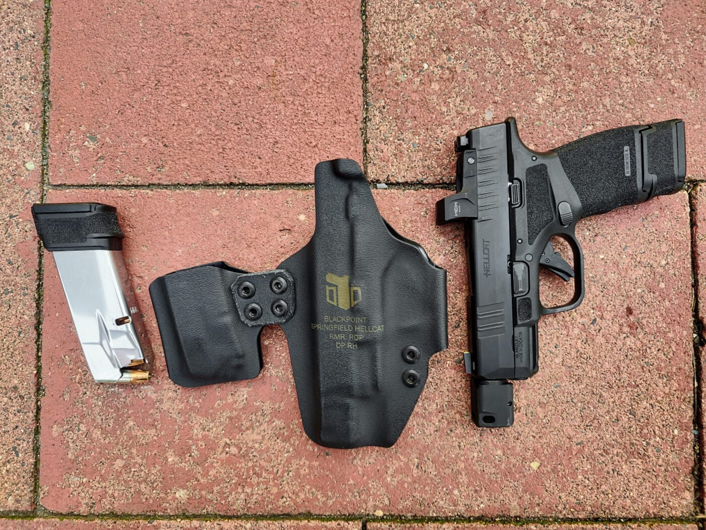 Hellcat pistol and magazine shown with DualPoint AIWB holster