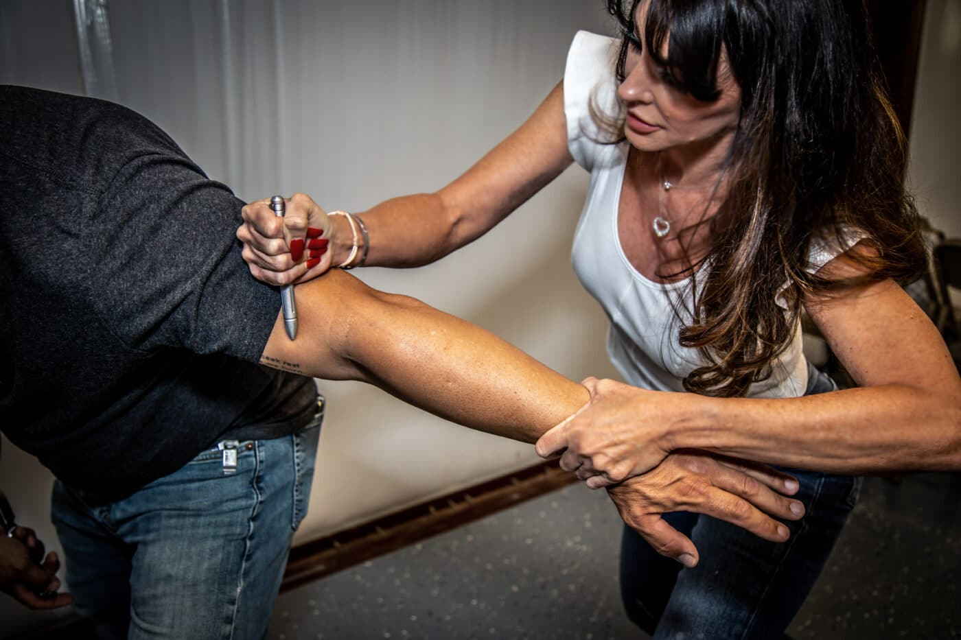 Woman using an arm bar takedown with a tactical pen