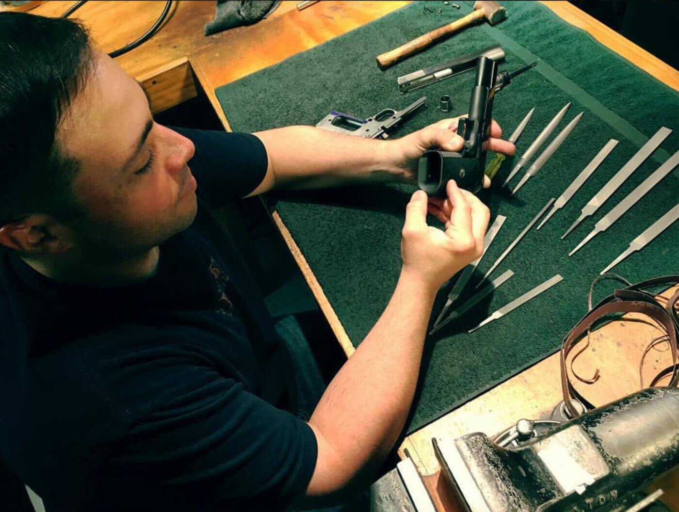Jason Burton inspecting a custom pistol