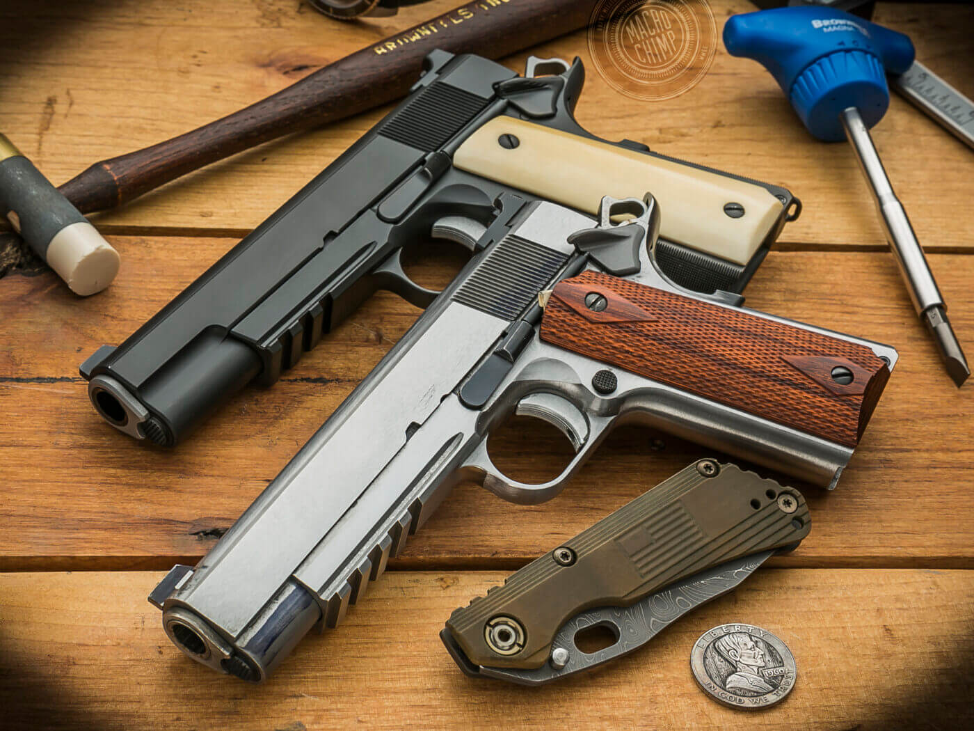 Custom built Springfield 1911 pistols on a table with tools