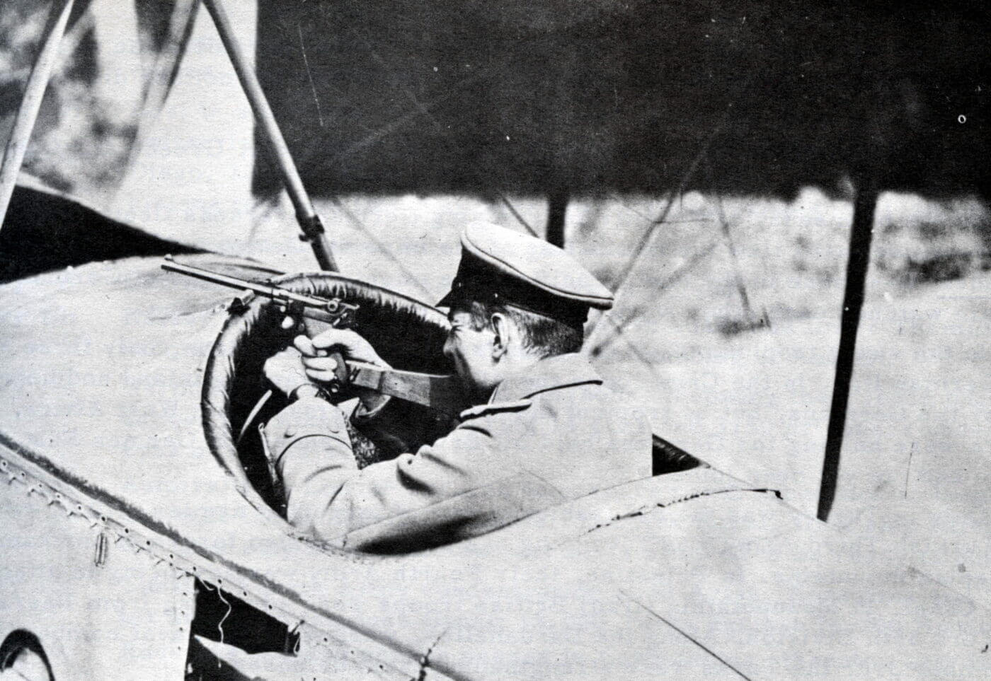 Luger being used by pilot in early airplane