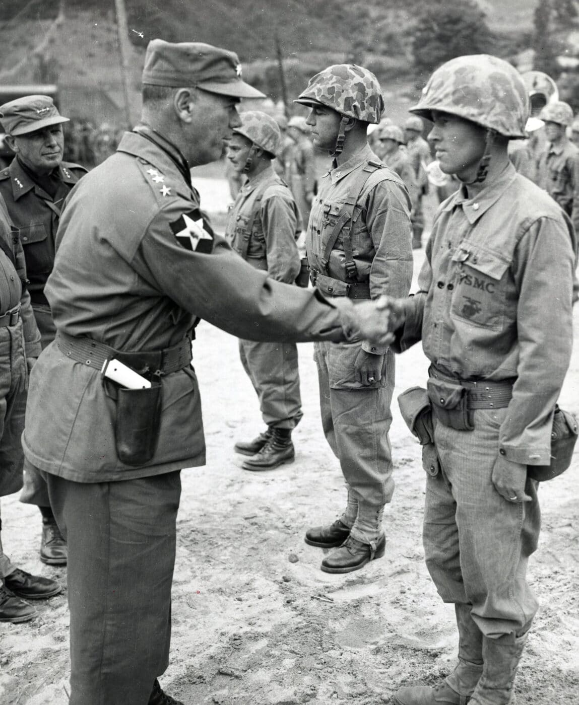 Lieutenant General James Van Fleet shakes hands with a soldier in the Korean War while carrying a 1911 pistol