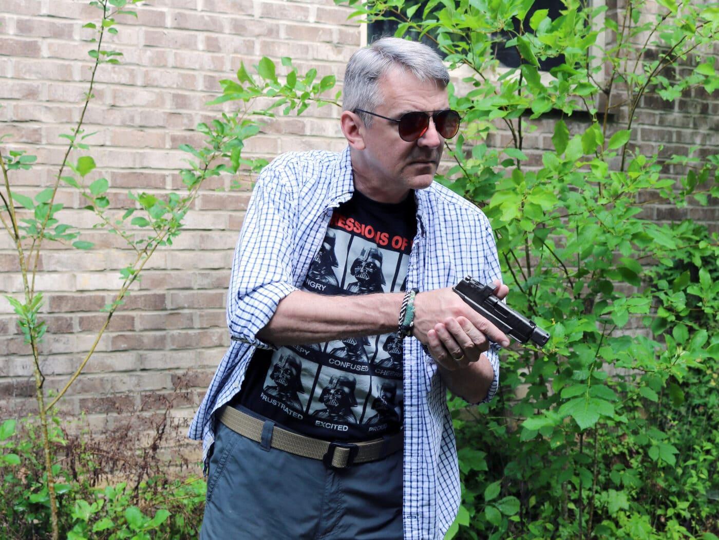 Man holding Springfield Armory Hellcat RDP pistol and using DeSantis holster