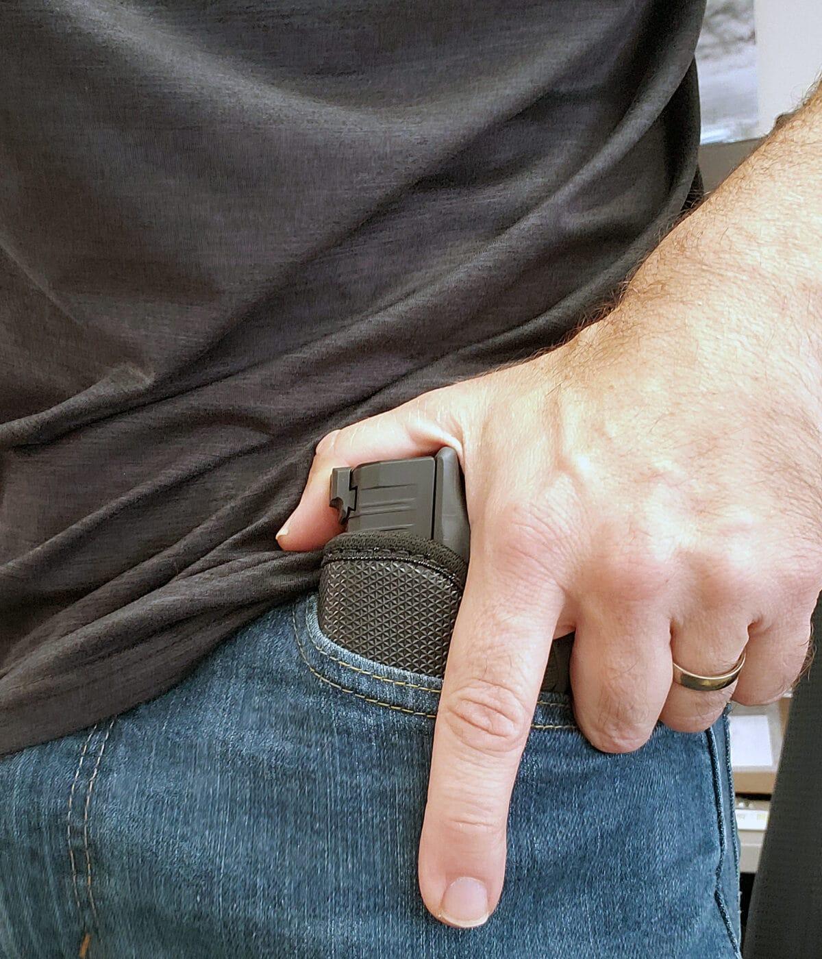 Man drawing Springfield Hellcat in Galco StukOn-U pocket holster from pocket