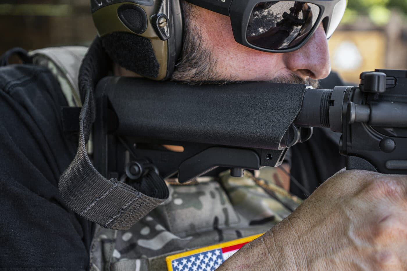 Man holding rifle and showing the attachment location of sling