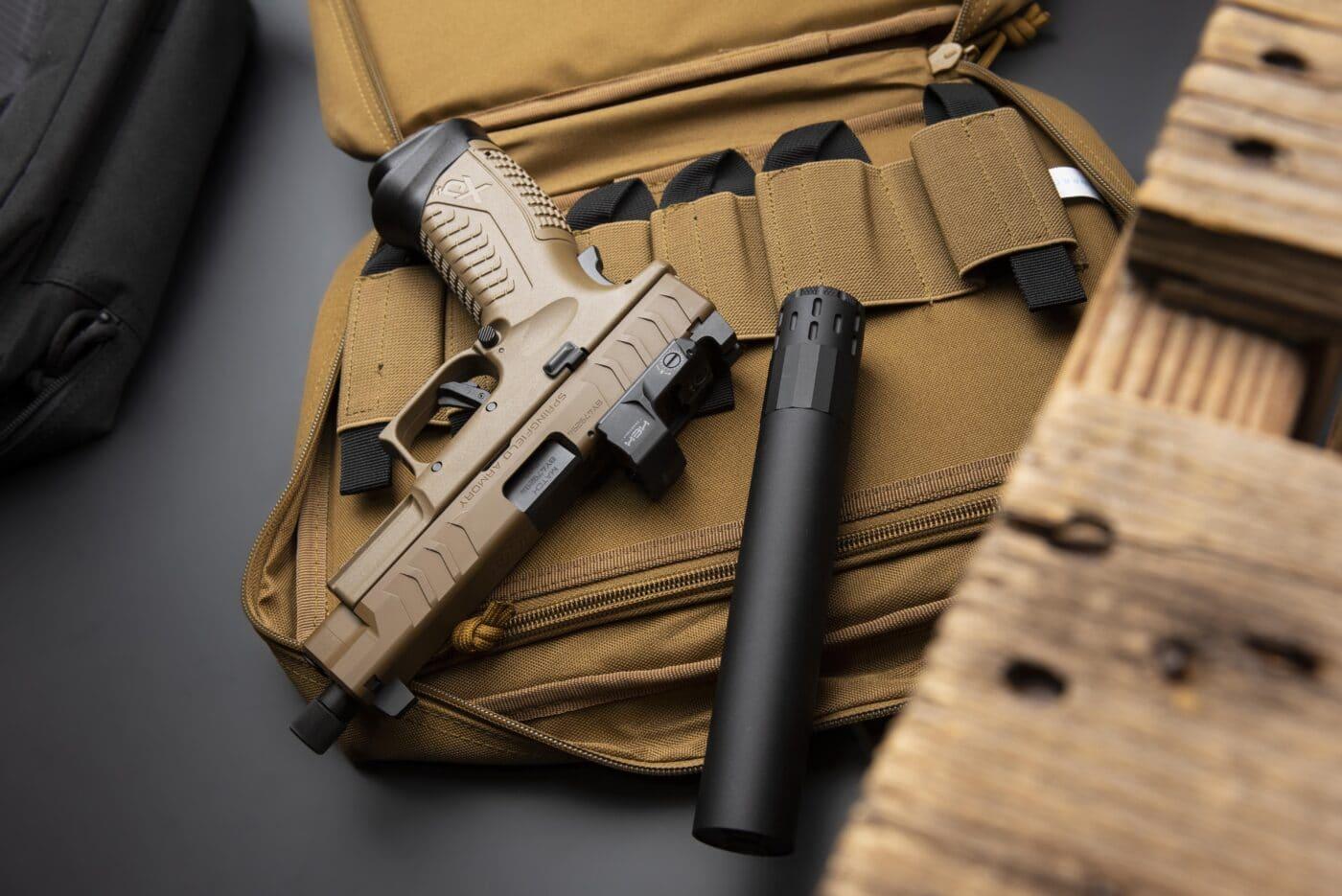 Multi-caliber suppressor sitting next to pistol