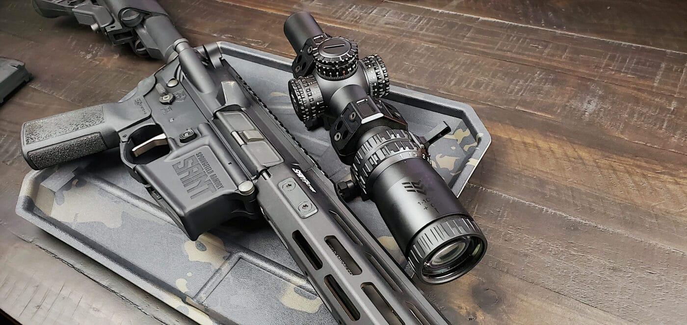 Swampfox Arrowhead rifle scope next to a SAINT rifle
