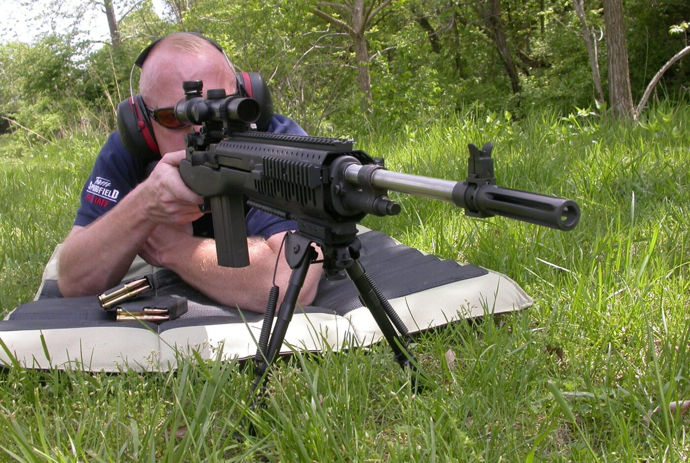 Man shooting a rifle from a prone position with bipod